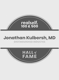 Realself logo for their top 100 and top 500 hall of fame award for Dr. Kulbersh's Charlotte plastic surgery center